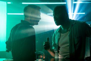 James Bond (Daniel Craig) talks to Felix Leiter (Jeffrey Wright) in a nightclub in Jamaica in NO TIME TO DIE