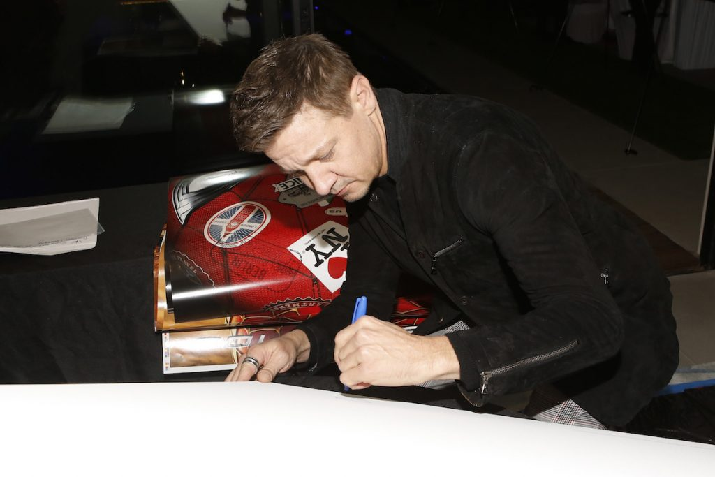 Jeremy Renner signing items for the Aiding Australia Benefit. (Photo by: David Yeh)