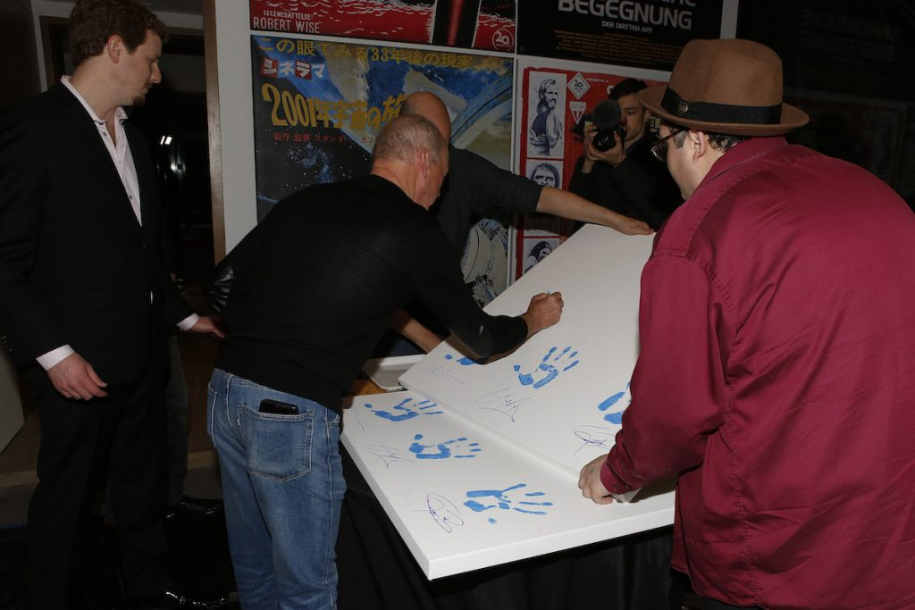 Michael Keaton signs an item for the Aiding Australia Benefit (Photo by: David Yeh)